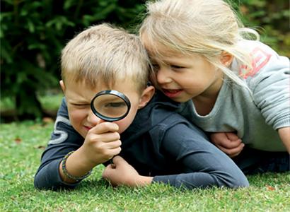 2 enfants scrutent l'herbe